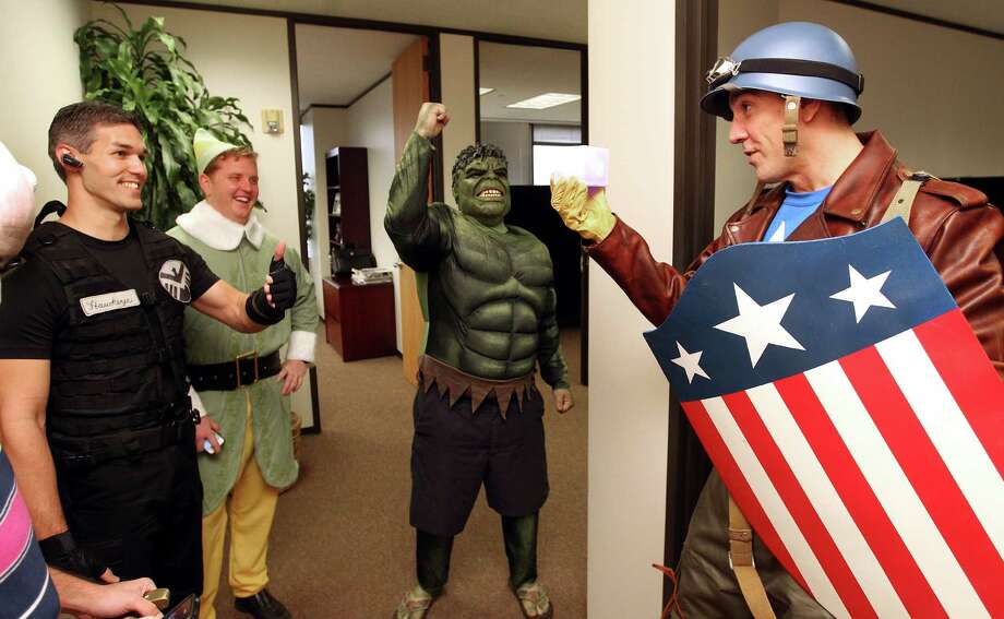 At left, Clint Akin, dressed as Hawkeye from the movie The Avengers, Mike Becherer, dressed as Buddy the Elf from the movie Elf, and Tim Lancaster dressed as the Incredible Hulk, show their approval to Chauncey Roschbach as he walked out of his office dressed as Captain America from the movie Captain America: The First Avenger, where he is a senior information technology manager at a oil and gas equipment online auction company Friday, Oct. 26, 2012, in Houston. 