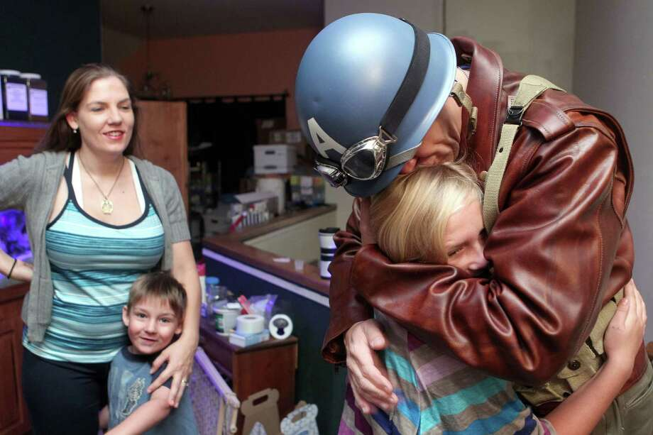 Dressed as Captain America from the movie Captain America: The First Avenger, Chauncey Roschbach, kisses his daughter Felicity, 9, next to his wife Sabrina and daughter Felicity, 9, as he left his Pearland home for work where his is a senior information technology manager at a oil and gas equipment online auction company Friday, Oct. 26, 2012. Roschbach said he made most of the costume himself, which he had been planning since July, including dying his leather jacket, sanding and painting the WWll era helmet and making his shield and T-shirt. Photo: Johnny Hanson, Houston Chronicle / © 2012  Houston Chronicle