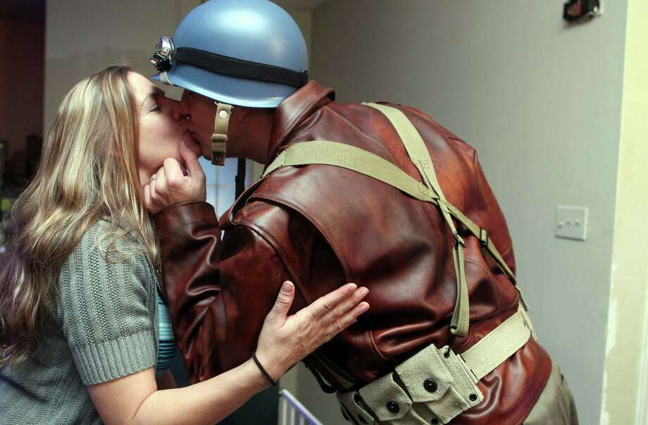 Dressed as Captain America from the movie Captain America: The First Avenger, Chauncey Roschbach, kisses his wife Sabrina, as he left his Pearland home for work where his is a senior information technology manager at a oil and gas equipment online auction company Friday, Oct. 26, 2012. Photo: Johnny Hanson, Houston Chronicle / © 2012  Houston Chronicle
