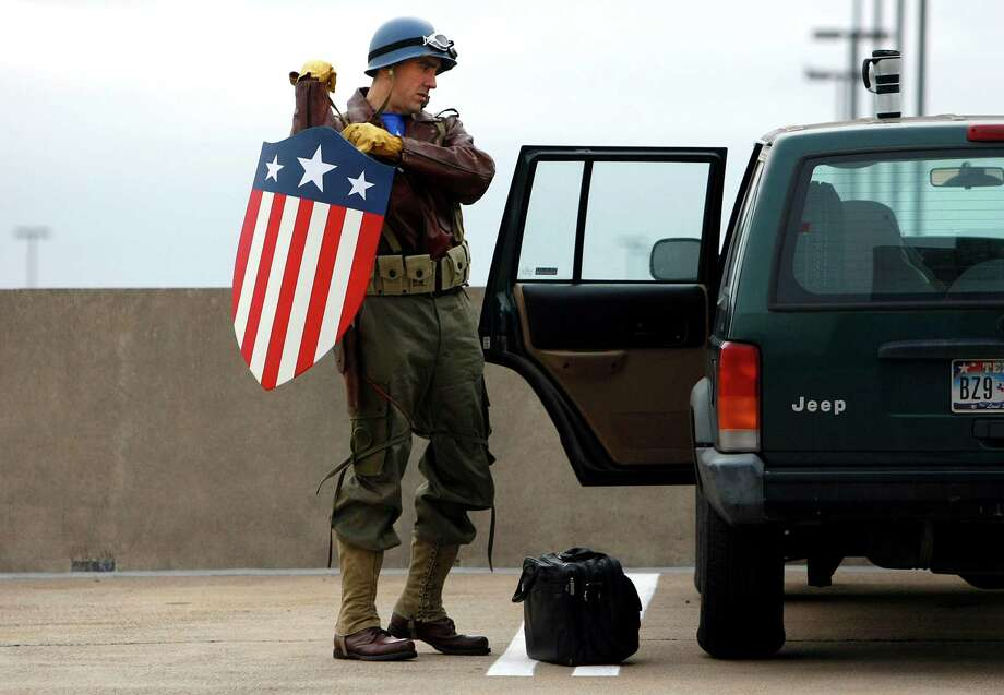Dressed as Captain America from the movie Captain America: The First Avenger, Chauncey Roschbach, assembles his costume to head into work where his is a senior information technology manager at a oil and gas equipment online auction company Friday, Oct. 26, 2012, in Houston. Photo: Johnny Hanson, Houston Chronicle / © 2012  Houston Chronicle