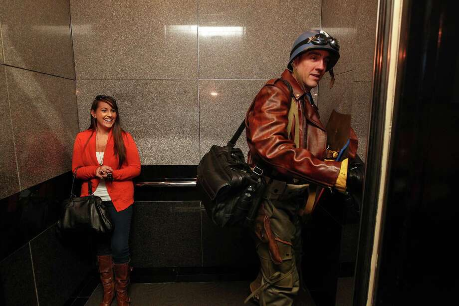 Kristin Price, left, laughs as Chauncey Roschbach, dressed as Captain America from the movie Captain America: The First Avenger, got on the elevator on his way to work where his is a senior information technology manager at a oil and gas equipment online auction company Friday, Oct. 26, 2012, in Houston. Photo: Johnny Hanson, Houston Chronicle / © 2012  Houston Chronicle