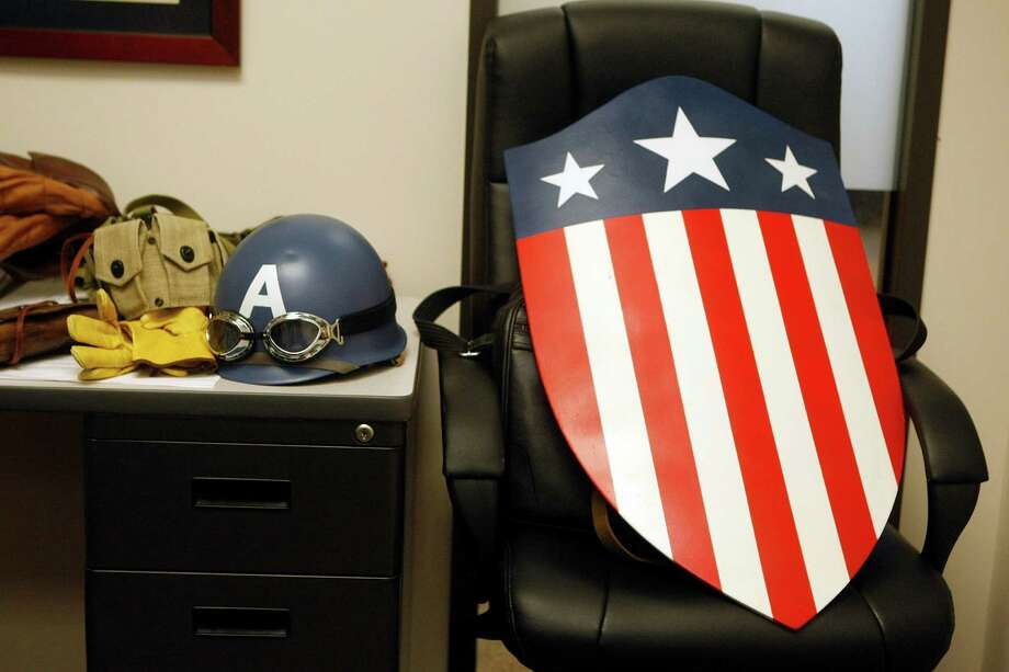 Chauncey Roschbach, who was dressed as Captain America from the movie Captain America: The First Avenger, leaves part of his costume aside as he settled into his office to start work where his is a senior information technology manager at a oil and gas equipment online auction company Friday, Oct. 26, 2012, in Houston. Photo: Johnny Hanson, Houston Chronicle / © 2012  Houston Chronicle