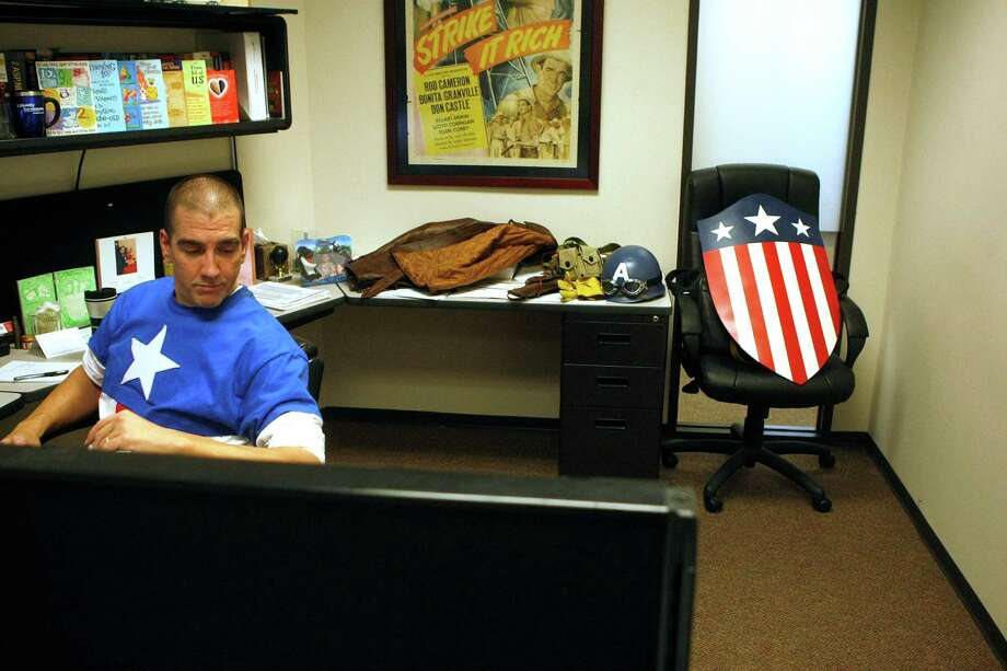Chauncey Roschbach, dressed as Captain America from the movie Captain America: The First Avenger, settles into his office to start work where his is a senior information technology manager at a oil and gas equipment online auction company Friday, Oct. 26, 2012, in Houston. Photo: Johnny Hanson, Houston Chronicle / © 2012  Houston Chronicle