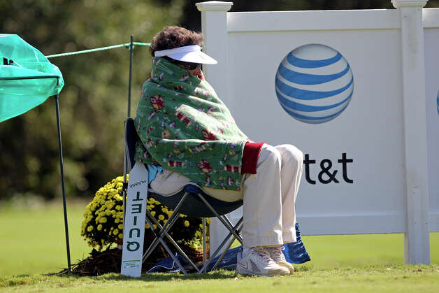 Volunteer Cindy Tuerk tries to stay warm under a blanket on the second teebox during the 2012 AT&T Championship at the AT&T Canyons course on October 26, 2012. Photo: Tom Reel, Express-News / ©2012 San Antono Express-News