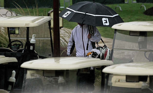 Golf bags get yanked off carts as a thunderstorm hits early during the first round of the 2012 AT&T Championship at the AT&T Canyons course on October 26, 2012. Photo: Tom Reel, Express-News / ©2012 San Antono Express-News