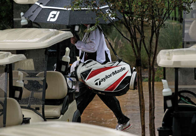 Golfers scamper off the course as an early thunderstorm stops play at the 2012 AT&T Championship at the AT&T Canyons course on October 26, 2012. Photo: Tom Reel, Express-News / ©2012 San Antono Express-News