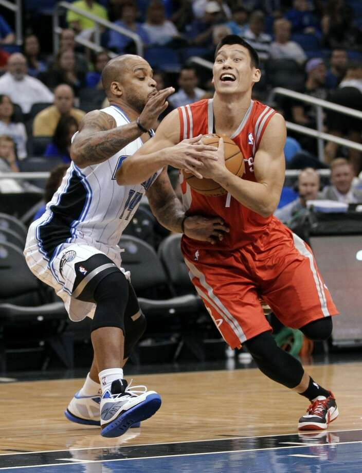 Rockets point guard Jeremy Lin, right, drives around Magic guard Jameer Nelson during the first half. (John Raoux / Associated Press)
