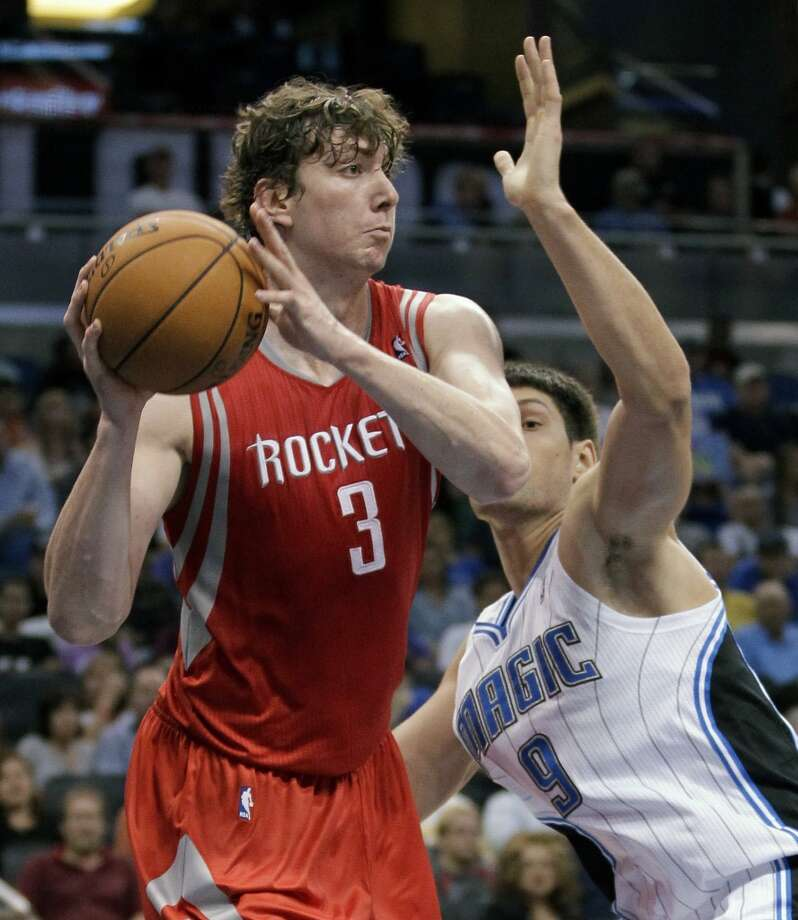 Rockets center Omer Asik tries to pass around Nikola Vucevic of the Magic. (John Raoux / Associated Press)