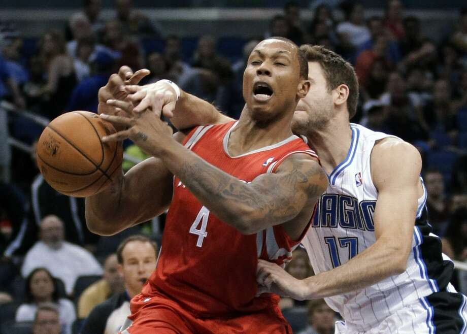 Rockets center Greg Smith gets fouled by Magic forward Josh McRoberts during the first half. (John Raoux / Associated Press)