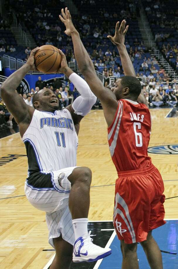 Magic forward Glen Davis attempts a shot over Rockets forward Terrence Jones. (John Raoux / Associated Press)