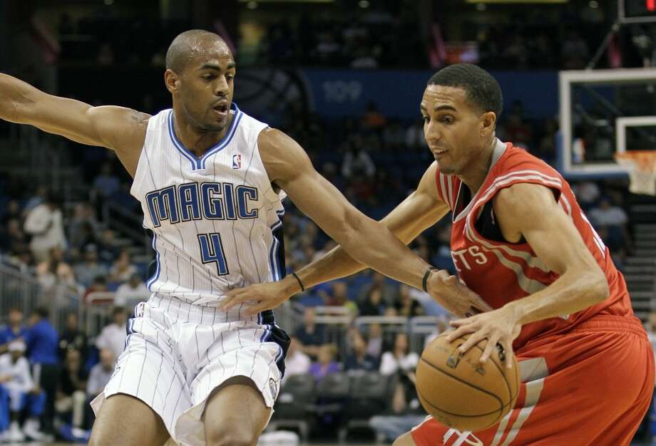 Rockets guard Kevin Martin is defended by Magic forward Arron Afflalo. (John Raoux / Associated Press)