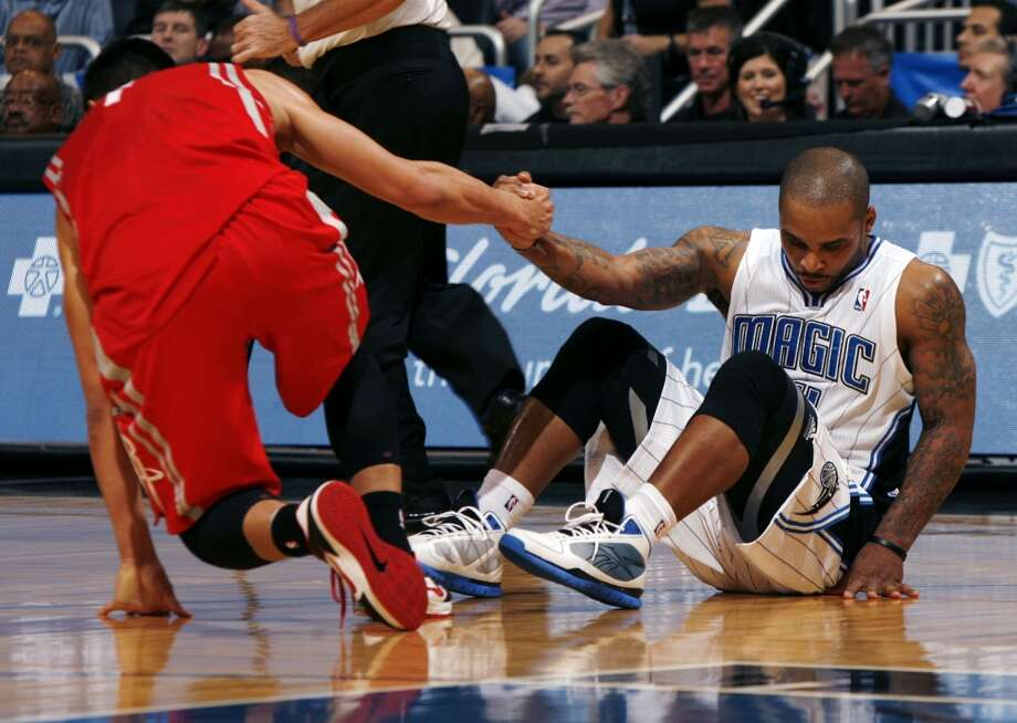 Rockets point guard Jeremy Lin helps up Magic guard Jameer Nelson. (Stephen M. Dowell / Orlando Sentinel/MCT)