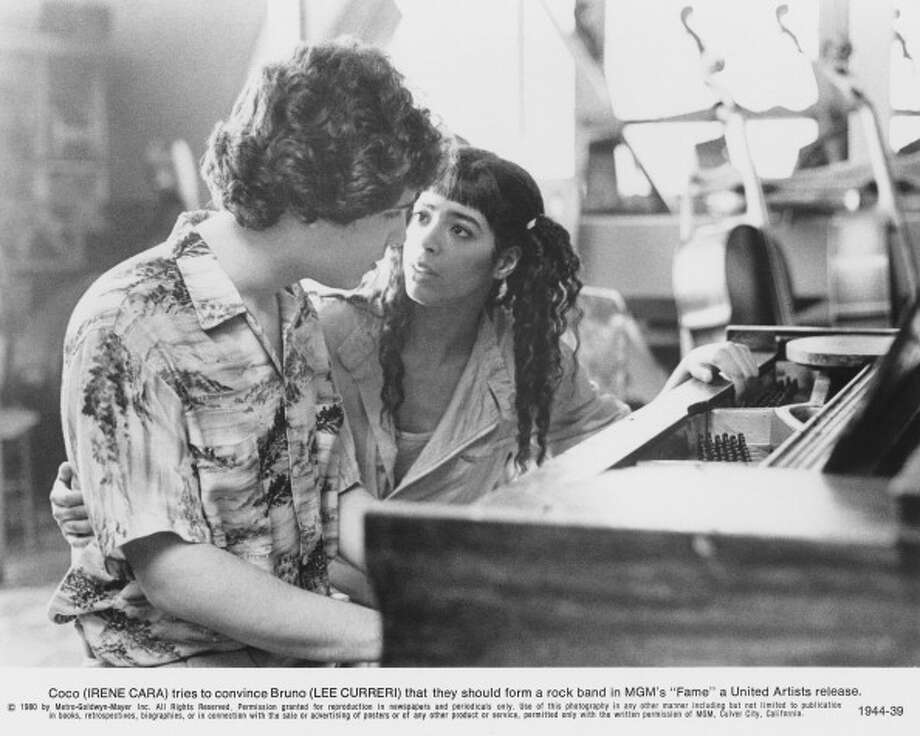 """Fame! I'm gonna live forever! Irene Cara belted out the theme song of the 1980 movie """"Fame,"""" in which she played Coco Hernandez, who in this scene, is listening to Bruno tell her why they should form a rock band. The movie spawned a TV series. Photo: United Artists, . / 2011 Getty Images"""