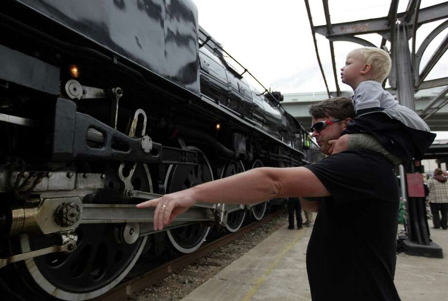 Michael Floyd carries son Christopher Floyd while they view the Union Pacific Steam Train shortly after its arrival to the Amtrak Station in Downtown Houston to kickoff Union Pacific Railroad's 150th Anniversary Celebration on Friday, Oct. 26, 2012, in Houston. Photo: Mayra Beltran, Houston Chronicle / © 2012 Houston Chronicle