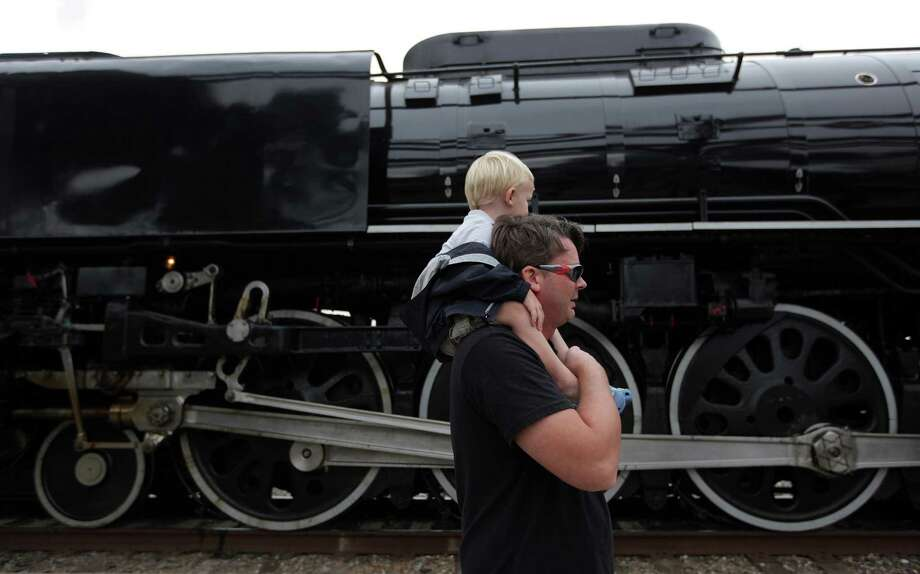 Christopher Floyd is carried by father Michael Floyd shortly after the Union Pacific Steam Train arrives to the Amtrak Station in Downtown Houston to celebrate Union Pacific Railroad's 150th Anniversary on Friday, Oct. 26, 2012, in Houston. Photo: Mayra Beltran, Houston Chronicle / © 2012 Houston Chronicle