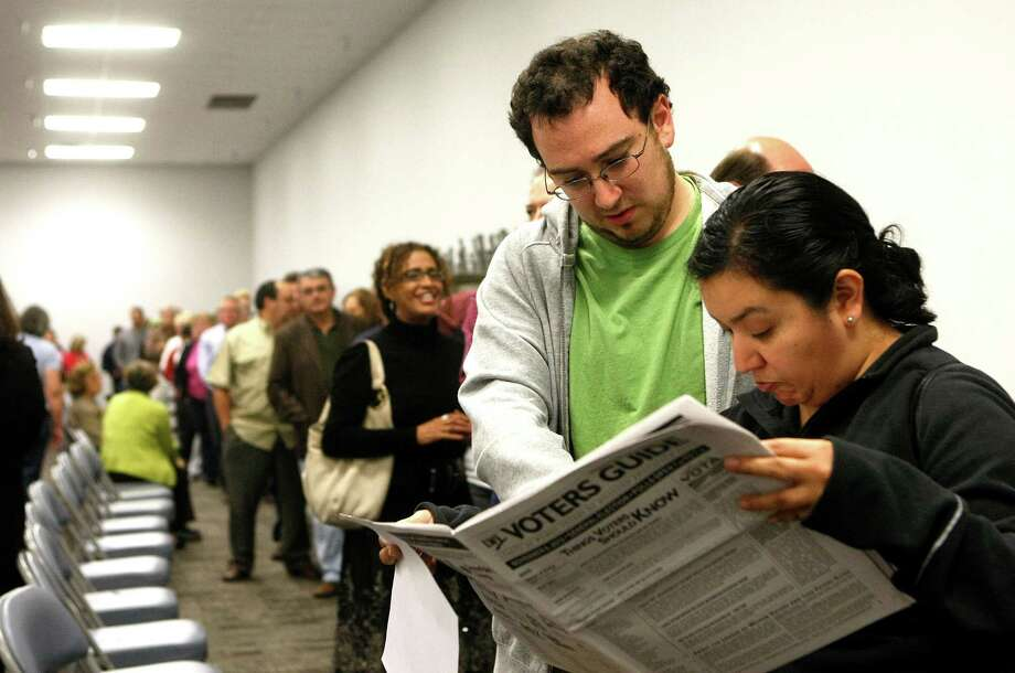 David Zaga and Monica Ortega read a Voters Guide while waiting in line to vote during early voting at the Harris County Precinct 3 Trini Mendenhall Sosa Community Center Friday, Oct. 26, 2012, in Houston. The numbers of voters were so great at the location, some had to wait more than an hour to vote. Photo: Johnny Hanson, Houston Chronicle / © 2012  Houston Chronicle
