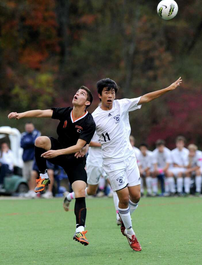 Stamford's Gustavo Torrealba, left, and Wilton's Matthew Chann, right, head the ball at the same time during Friday's FCIAC boys soccer quarterfinal game at Wilton High School on October 26, 2012. Photo: Lindsay Niegelberg
