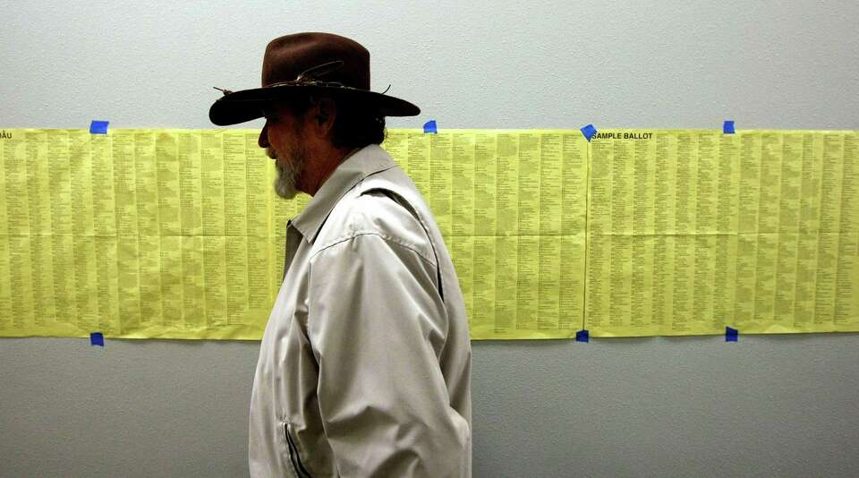 Ted Ballinger walks past a sample ballot to vote during early voting at the Harris County Precinct 3