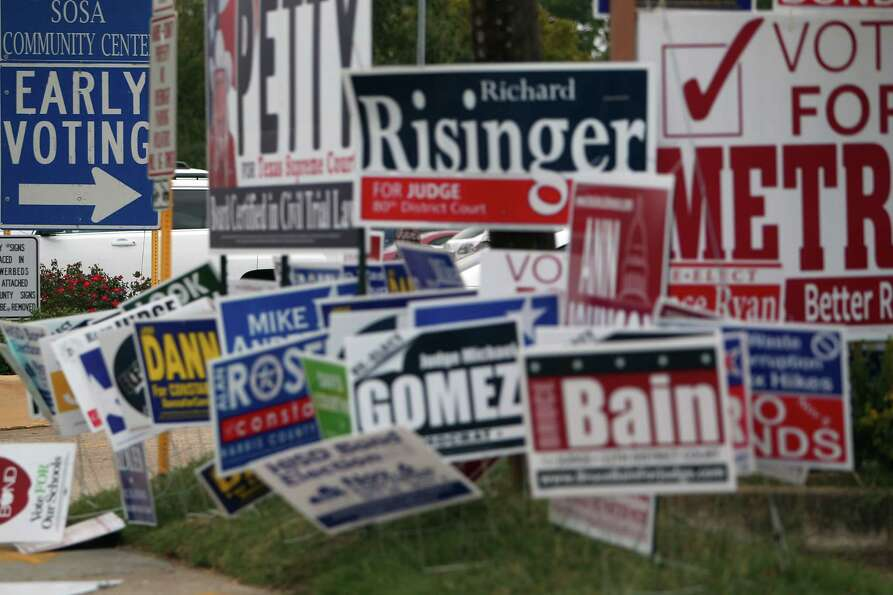 Campaign signs litter the area outside early voting at the Harris County Precinct 3 Trini Mendenhall