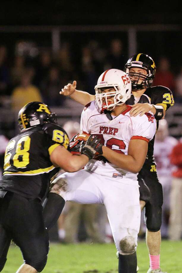 Mike Ross Connecticut Post freelance - Fairfield Prep's # 66 Anthony Palazzolo intercepts as Amity High School's #32 David Buono and # 68 Gregory Purcell atempt to break up play during first half action on Friday evening. Photo: Mike Ross