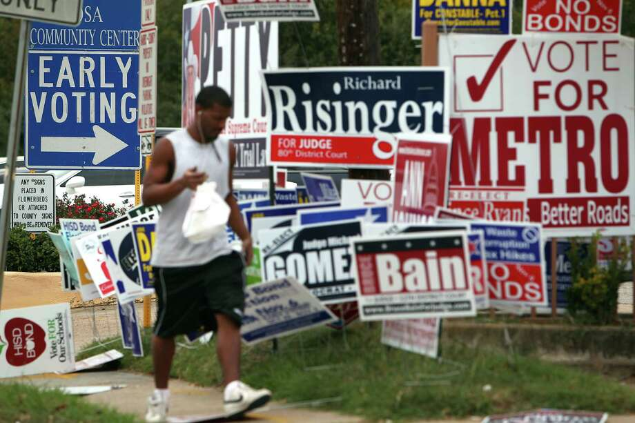 His lunch in hand, Zachary Brown walks past a group of campaign signs littering the area outside early voting at the Harris County Precinct 3 Trini Mendenhall Sosa Community Center Friday, Oct. 26, 2012, in Houston. Brown said he plans on voting this election but probably will not vote during early voting. Photo: Johnny Hanson, Houston Chronicle / © 2012  Houston Chronicle