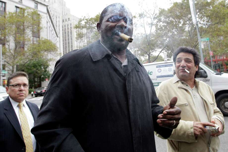 "Former New York Giants linebacker Lawrence Taylor smokes a ""redemption"" cigar as he leaves federal court Friday after winning the lawsuit. Photo: Mary Altaffer, STF / AP"
