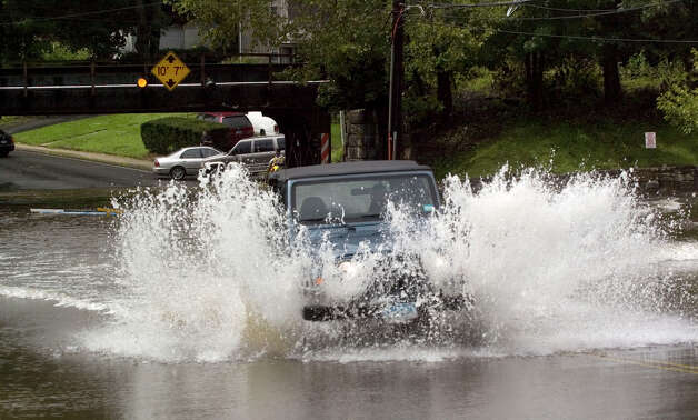 A vehicle successfully attempts to drive through the rushing water along West Street in Danbury due to Hurricane Irene on Sunday, Aug. 28, 2011. Photo: Jason Rearick