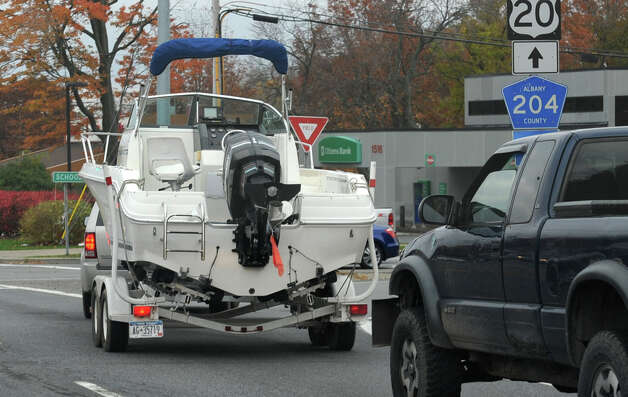 A boat pulled by a truck turns onto Schoolhouse Rd. from Western Ave.  on Friday, Oct. 26, 2012 in Guilderland, N.Y. Boaters taking advantage of warm fall weather who still have their vessels docked should act now to secure them in advance of anticipated high winds and heavy rains from Hurricane Sandy. (Lori Van Buren / Times Union) Photo: Lori Van Buren