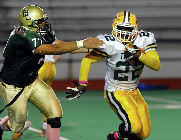 Bassick's #77 Juan Santos charges towards Trinity Catholic's #22 Shaquan Howsie, during boys football action in Bridgeport, Conn. on Friday October 26, 2012. Photo: Christian Abraham