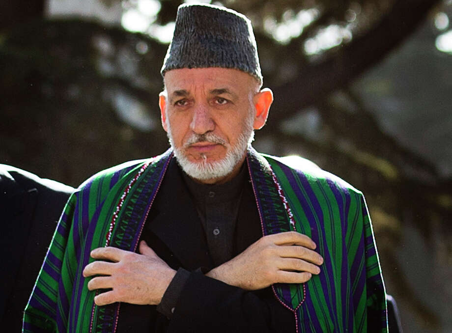 Afghan President Hamid Karzai arrives to  review the guard of honor, during the first day of Eid Al Adha celebrations at the palace in Kabul, Afghanistan, Friday, Oct 26, 2012. Karzai called on Taliban to embrace peace and to join the government and lay down their arms. (AP Photo/Anja Niedringhaus) Photo: Anja Niedringhaus, STF / AP
