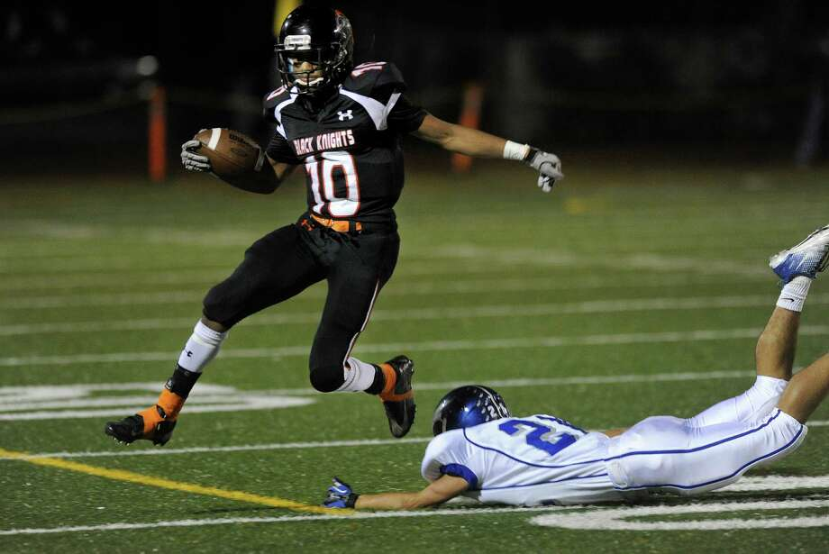 Stamford's John Pasard leaps over Fairfield Ludlowe's Bryan Pacewicz during Friday's football game against Fairfield Ludlowe at Stamford High School on October 26, 2012. Photo: Lindsay Niegelberg