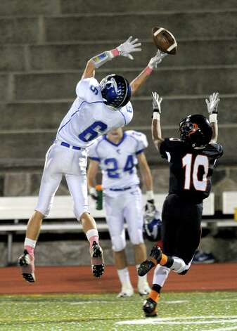 Fairfield Ludlowe's Dan Santella, left, and Stamford's John Pasard, right, reach for a pass that fell incomplete during Friday's football game at Stamford High School on October 26, 2012. Photo: Lindsay Niegelberg