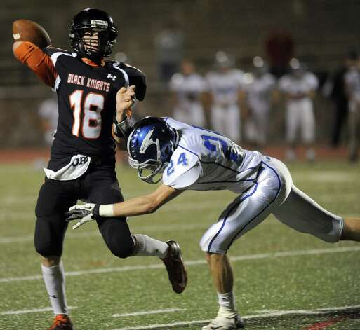 Stamford's Tyler Kane throws a pass just before being tackled by Fairfield Ludlowe's Kyle Dammeyer during Friday's football game at Stamford High School on October 26, 2012. Photo: Lindsay Niegelberg