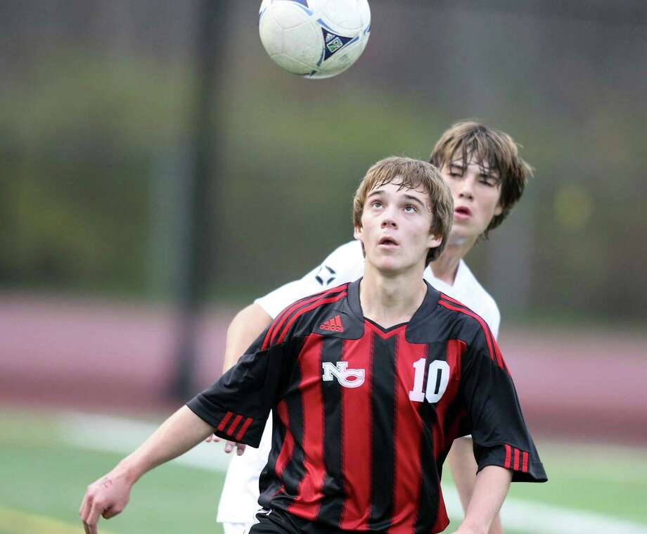 New Canaan soccer captain Stephen Valante keeps his eye on the ball as Ridgefield's Alexander Northcutt defends during FCIAC soccer action in Ridgefield on Friday night. Photo: J. Gregory Raymond