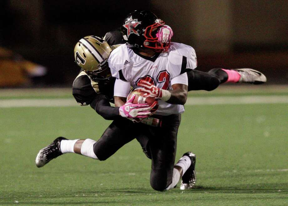 Terry running back Eugene Wright #22 is taken down by the face mask by Foster's Eric Jones #21 during a District 23-4A football game between the Terry Rangers and the Foster Falcons Friday, October 26, 2012. Photo: Bob Levey, Houston Chronicle / Houston Chronicle