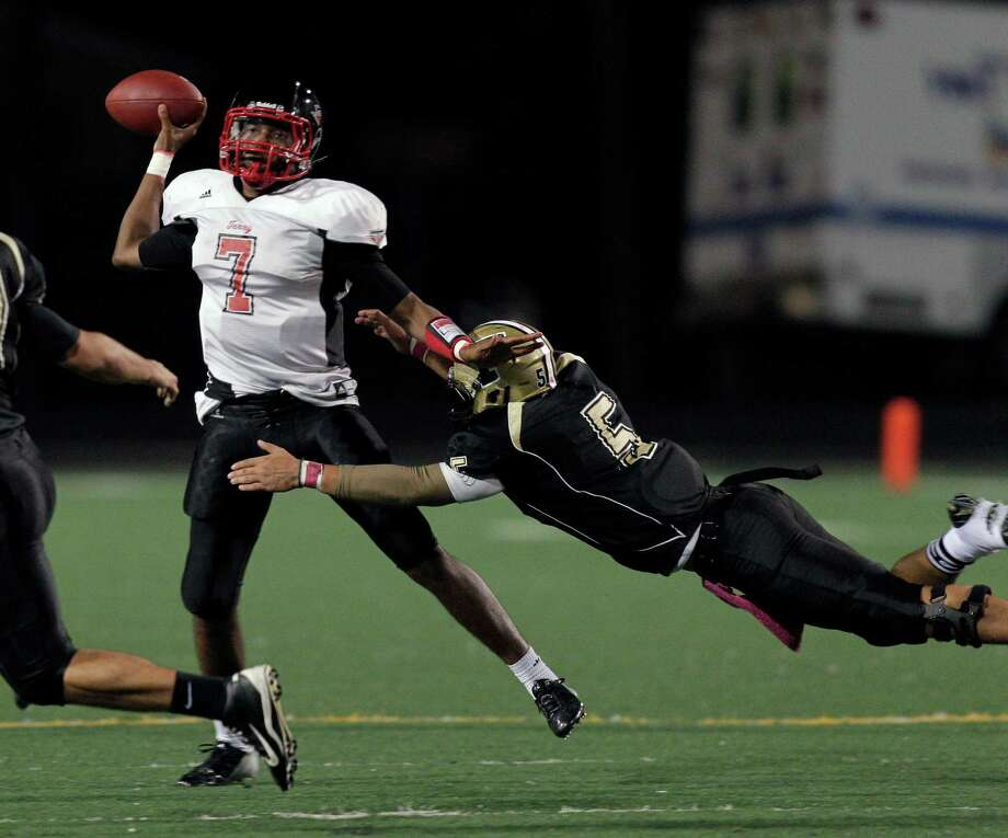 Terry quarterback Antoine Arboleda #7 rolls out as Foster's Evan Temple #57 applies pressure during a District 23-4A football game between the Terry Rangers and the Foster Falcons Friday, October 26, 2012. Photo: Bob Levey, Houston Chronicle / Houston Chronicle