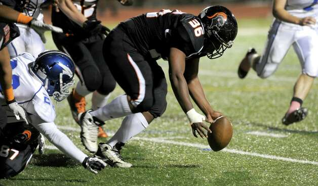 Stamford's Ryan Lapotts reaches to recover a loose ball during Friday's football game against Fairfield Ludlowe at Stamford High School on October 26, 2012. Photo: Lindsay Niegelberg