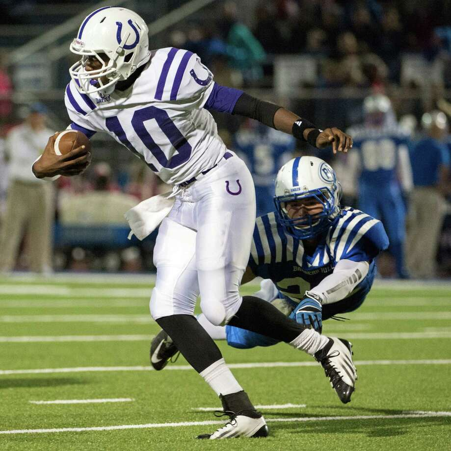 Dayton quarterback Markain Chambers (10) slips away from a Barbers Hill defender during the first half of a high school football game at Eagle Stadium, Friday, Oct. 26, 2012, in Mont Belvieu. Photo: Smiley N. Pool, Houston Chronicle / Houston Chronicle