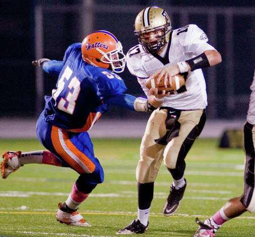 Danbury High School's Dezshawn Daley tries to grab Trumbull High School quarterback Nick Roberts during a game at Danbury. Friday, Oct. 26, 2012 Photo: Scott Mullin