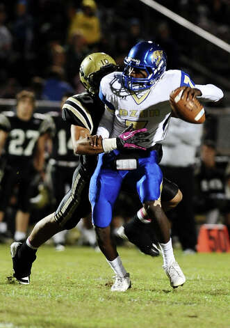 Ozen quarterback  Jordan Ozen, 7, is sacked by Nederland defensive back Sage Seay during the Nederland High School football game against Ozen High School at Nederland High School on Friday, October 26, 2012. Photo taken: Randy Edwards/The Enterprise Photo: Randy Edwards
