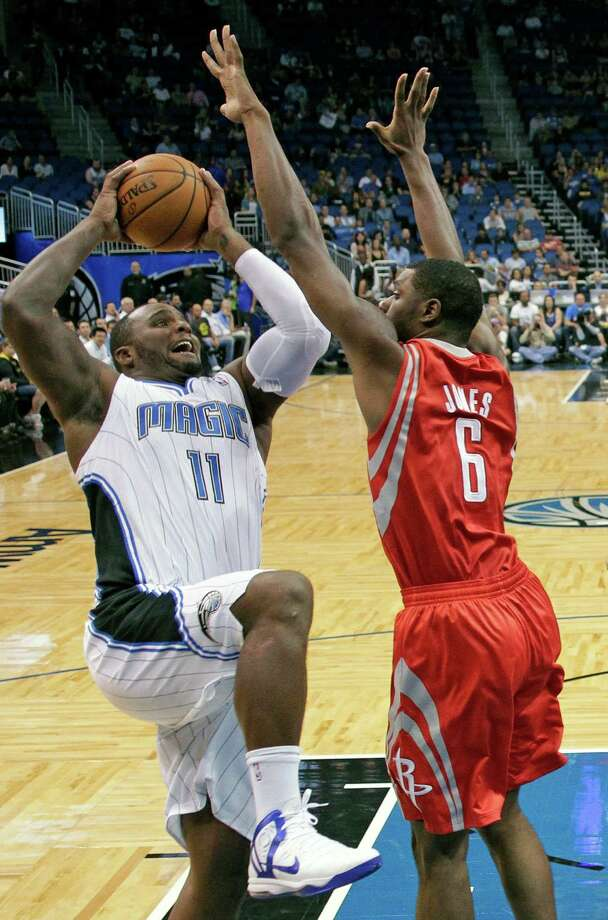 The Magic's Glen Davis, left, encounters a big hurdle on his drive in the form of Terrence Jones, who is looking like the Rockets' top backup at power forward. Photo: John Raoux, STF / AP