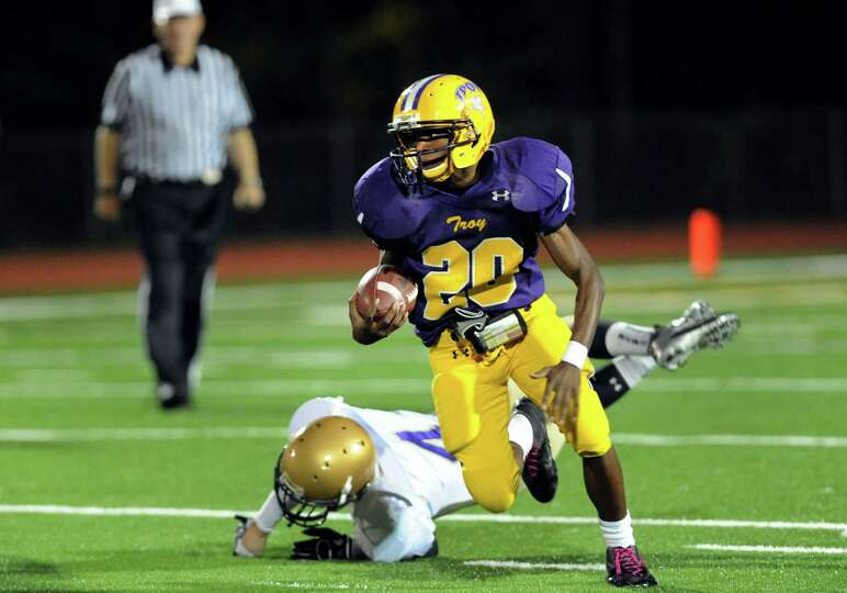 Troy's Maurice Jones (20), right, dodges a tackle from Amsterdam's Colbie Glionna (4) during their f