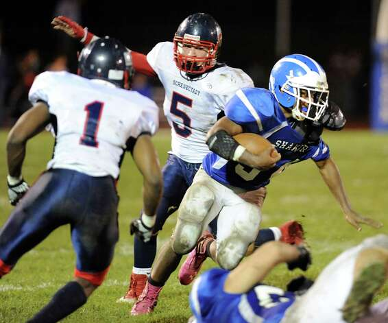 Shaker's Kenny Jackson (34), right, gains yards as Schenectady's Trent Wheeler (1), left, and Jeremy Kent (5) defend during their football game on Friday, Oct. 26, 2012, at Shaker High in Latham, N.Y. (Cindy Schultz / Times Union) Photo: Cindy Schultz / 00019848A
