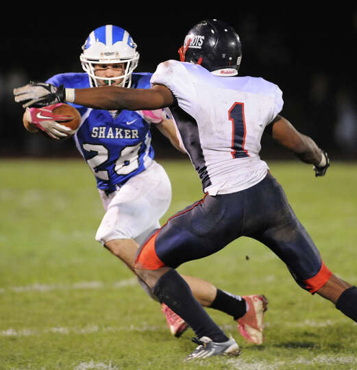 Shaker's Michael Lewis (28), left, gains yards as Schenectady's Trent Wheeler (1) defends during the