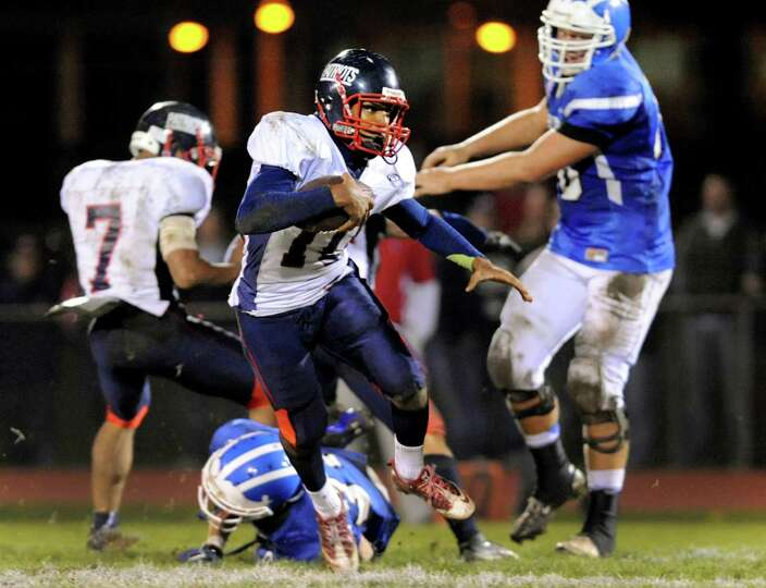 Schenectady's quarterback Kwame Jarvis (10), center, runs the ball during their football game agains