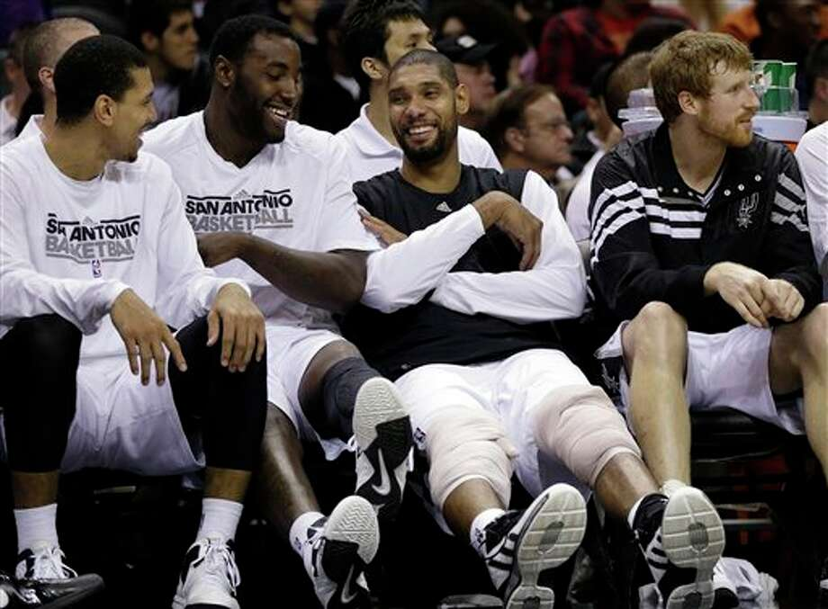 San Antonio Spurs' Tim Duncan, second from right, jokes with teammates, from left, Danny Green, DeJuan Blair, and Matt Bonner, right, as he ices his knees on the bench during the fourth quarter of an preseason NBA basketball game against the Washington Wizards, Friday, Oct. 26, 2012, in San Antonio. (AP Photo/Eric Gay) Photo: Eric Gay, AP / AP