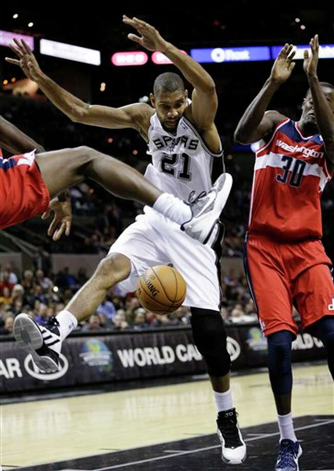 San Antonio Spurs' Tim Duncan, center, loses control of the ball as Washington Wizards' Martell Webster, left, and Earl Barron  (30) defend during the first quarter of an preseason NBA basketball game, Friday, Oct. 26, 2012, in San Antonio. (AP Photo/Eric Gay) Photo: Eric Gay, AP / AP