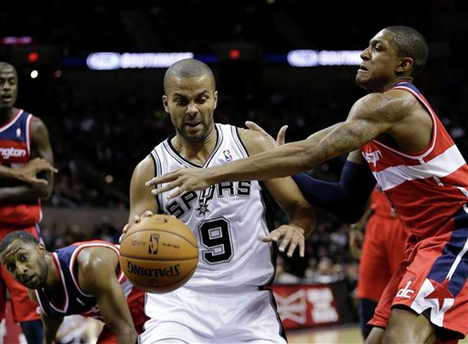 San Antonio Spurs' Tony Parker (9), of France,  drives to the basket as Washington Wizards' Bradley Beal, right, reaches in during the first quarter of an preseason NBA basketball game, Friday, Oct. 26, 2012, in San Antonio. (AP Photo/Eric Gay) Photo: Eric Gay, AP / AP