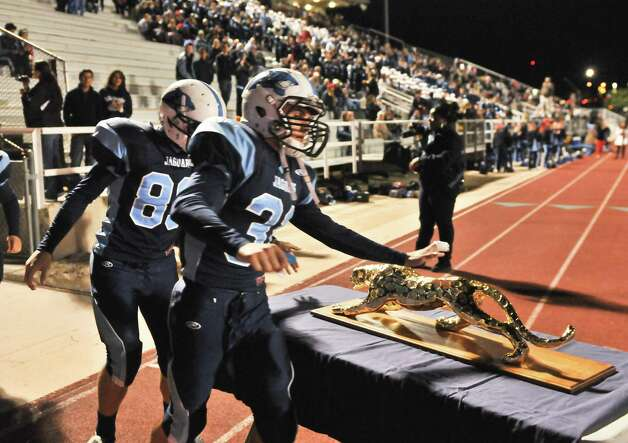Johnson players Xavier McElhannon (32) and Gavin Jones (89) touch the Jaguar whiile taking the field versus Reagan Friday night. Photo: Express-News