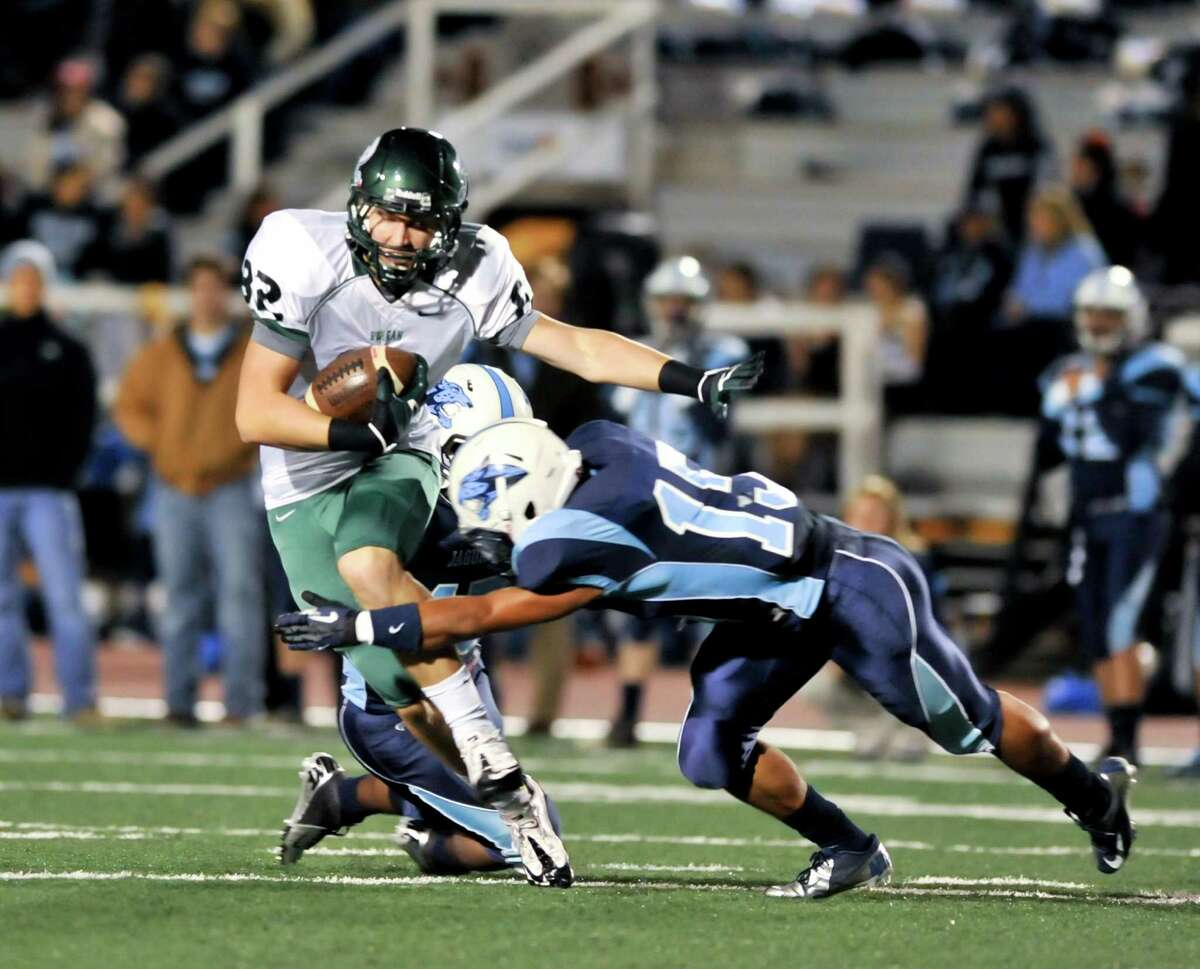 Reagan receiver John Grubb is tackled by Johnson's Fernando Cruz (15) after making a midfield catch.